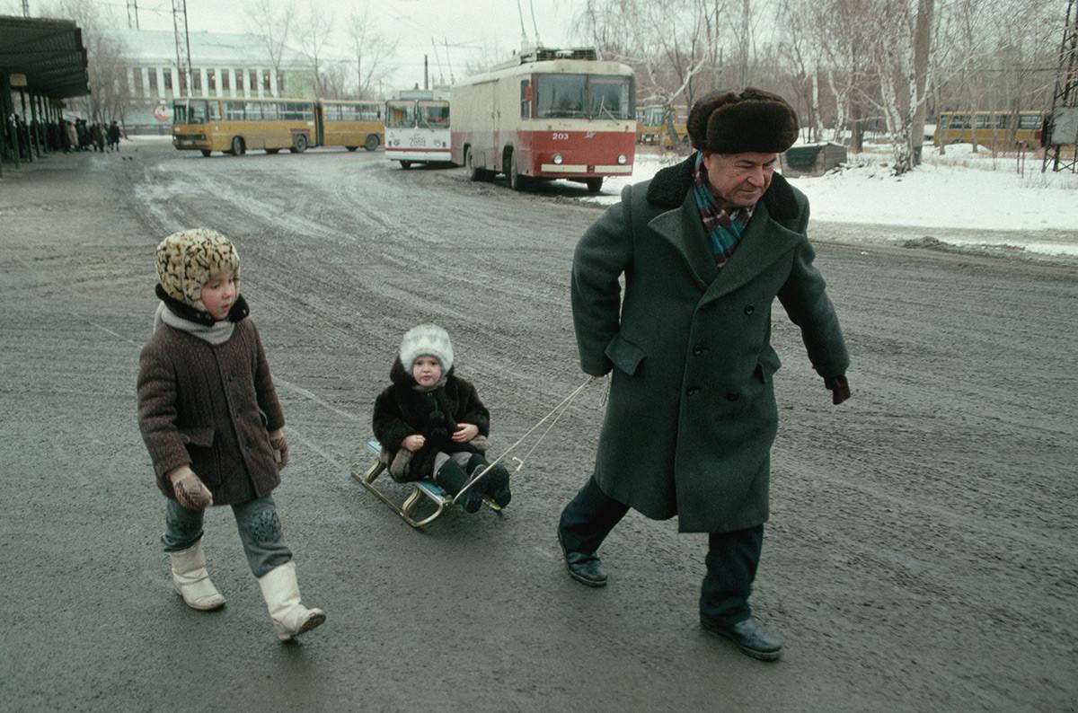 子どもをソリで引く男性