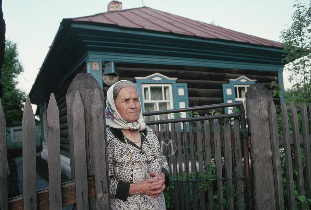 家の玄関先に立つシベリアの女性