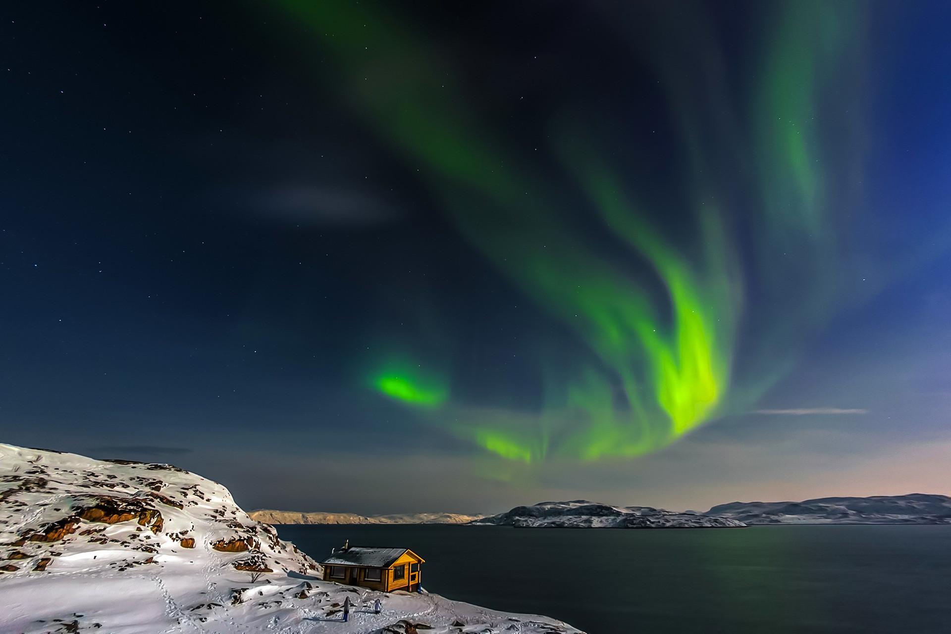Sebuah rumah sederhana di pesisir Laut Barents dengan Aurora di langit. Semenanjung Kola, Murmanskaya oblast.