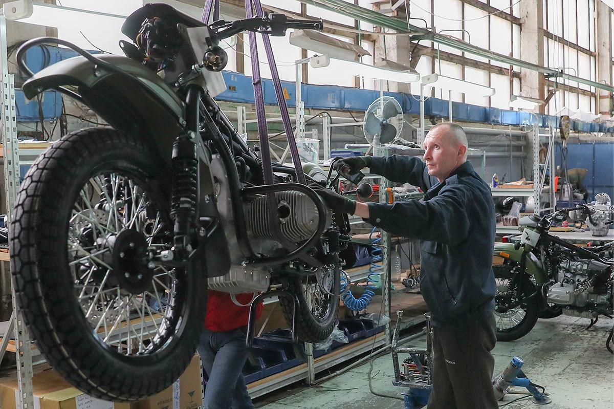Seorang pekerja tengah merakit sepeda motor Ural.