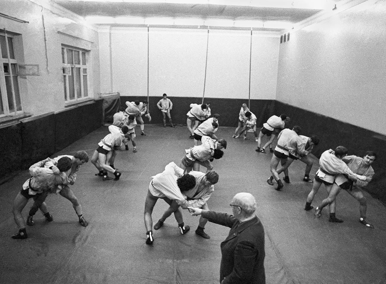 Заслуженный тренер СССР Анатолий Харлампиев , стоявший у истоков нового вида спорта самбо, во время занятий в секции