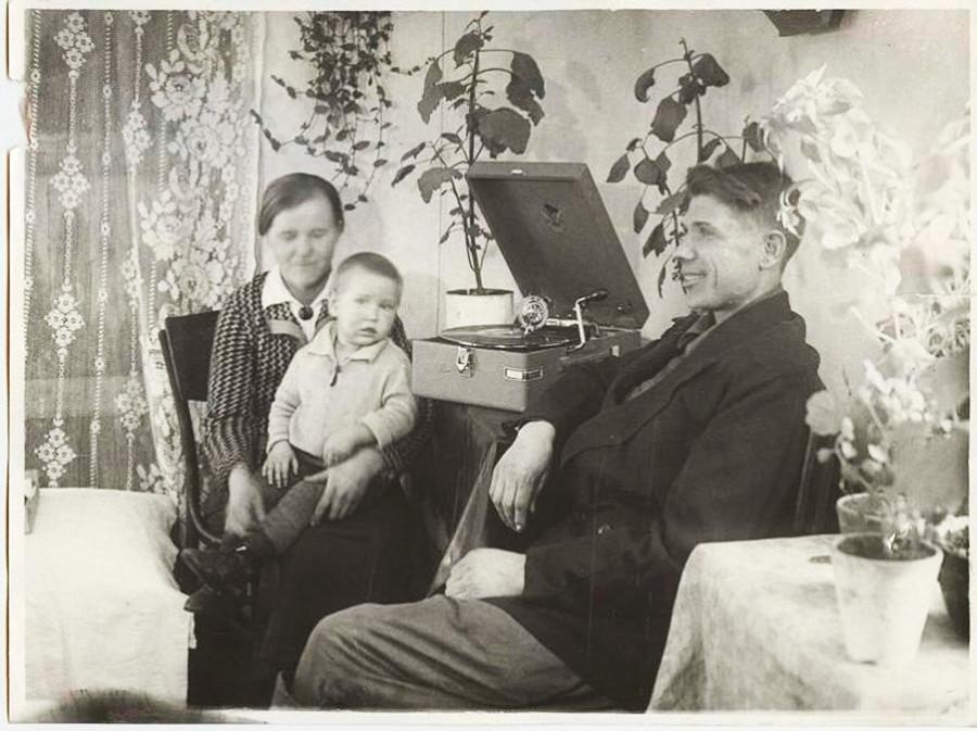 Le meilleur métallurgiste-stakhanoviste (travailleur exemplaire) de matériaux réfractaires du Combinat métallurgique de Magnitogorsk V. Bardakov et sa famille écoutent un gramophone dans leur appartement, 1936