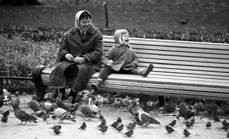 公園のベンチに座るおばあちゃんと孫、1960年代