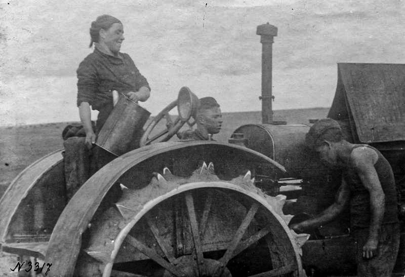 Une tractoriste travaille dans un village