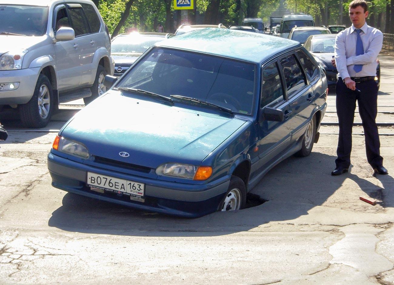 Власник поред аутомобила који је упао у јаму на Проспекту Лењина у Самари.
