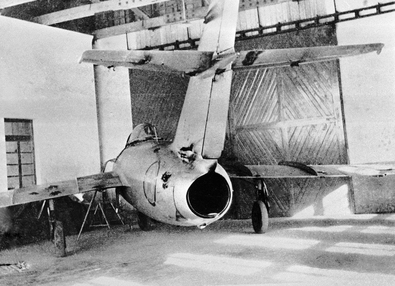 Sovjetski MiG-15 z vidnimi poškodbami na trupu, ki jih je prejel med zračnim bojem.