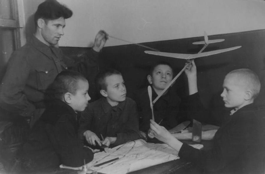 Des pionniers (équivalent soviétique des scouts) confectionnent un modèle réduit d'avion