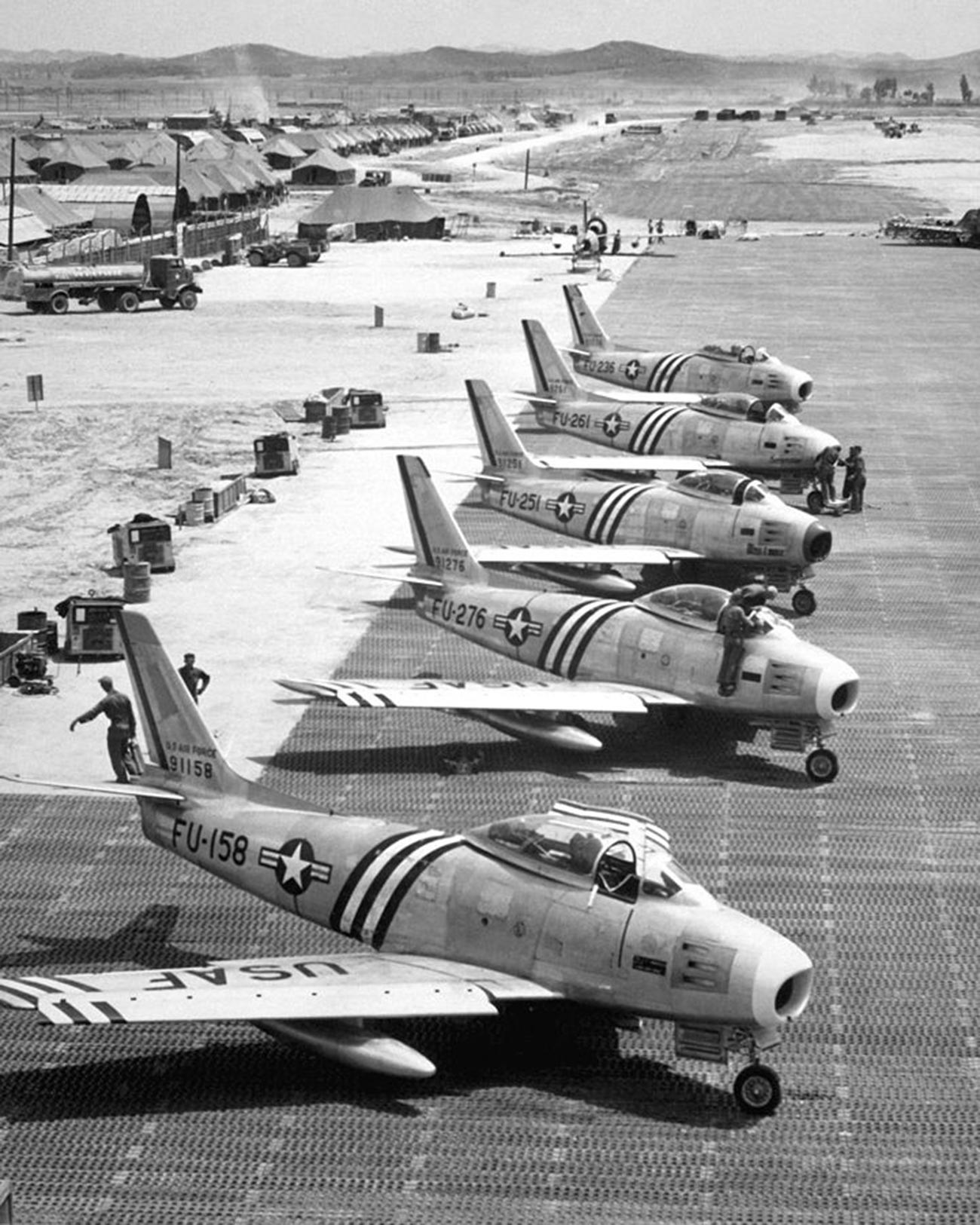 View of F-86 airplanes on the flight line getting ready for combat.