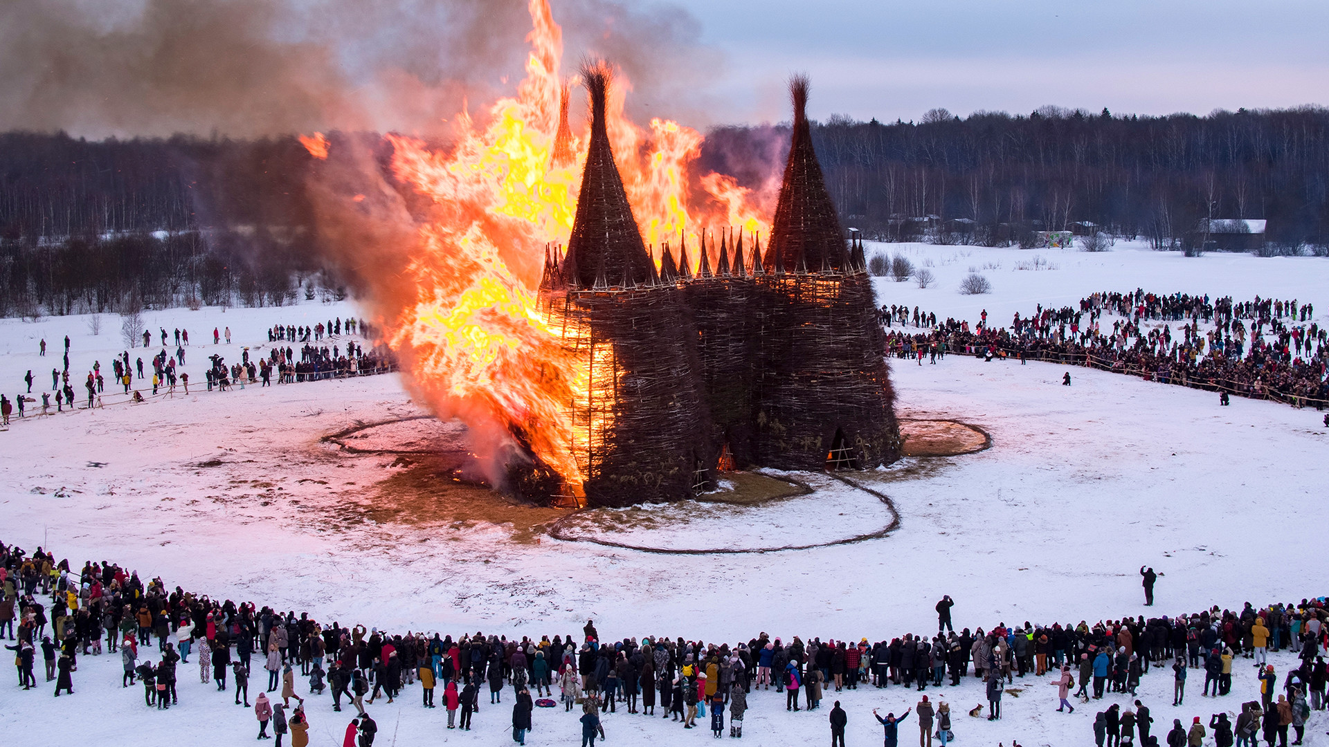 Orang-orang menyaksikan pembakaran kastil kayu sebagai bagian dari perayaan festival Maslenitsa di Desa Nikola-Lenivets, sekitar 200 kilometer di sebelah barat daya Moskow, Rusia, Sabtu (13/3).