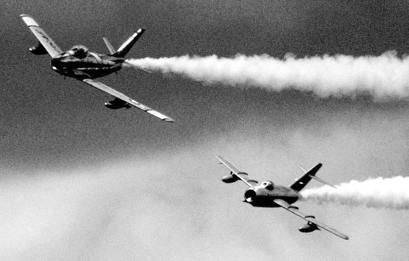 """Американски F-86 Сејбр (лево) од епохата на Корејската војна кого го брка МиГ-15 со севернокорејски обележја за време на симулирана битка на биеналето на аеромитингот во базата на Воздухопловната гарда на САД """"Селфриџ"""" кај Мичиген, 23 јули 2000 година."""