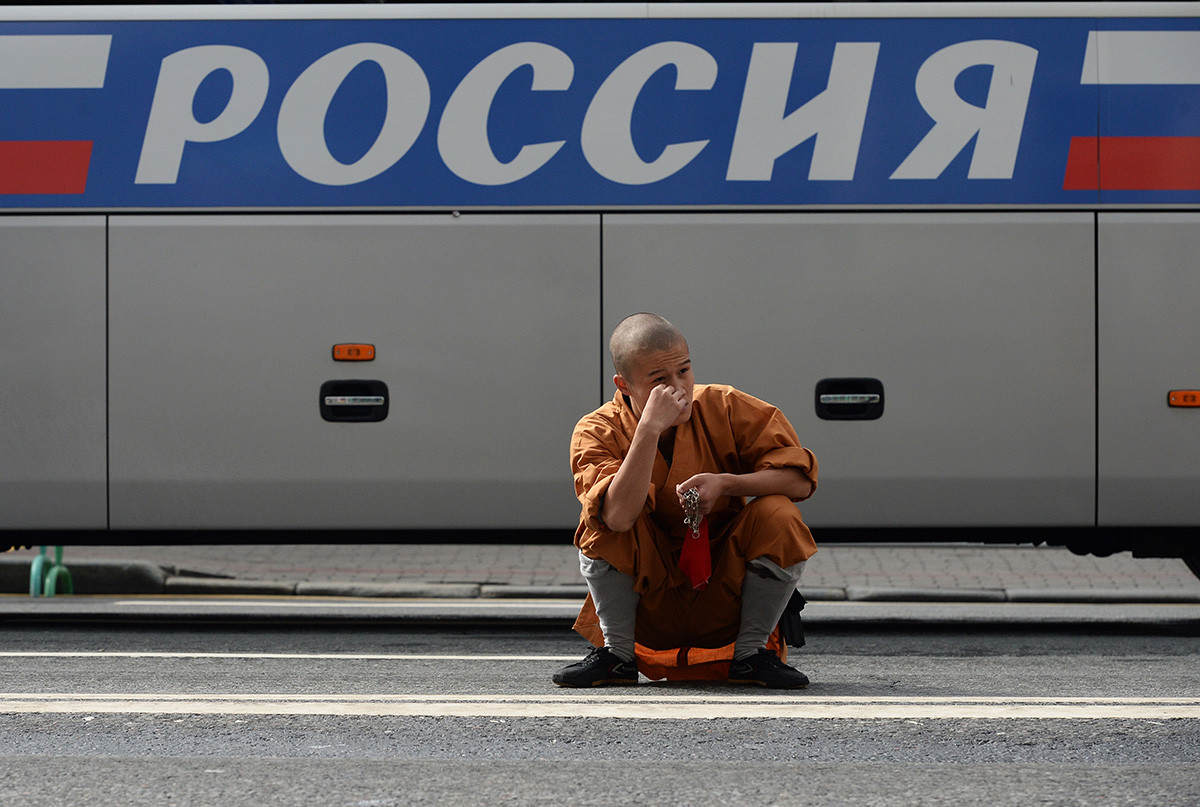 """Ein chinesischer Musiker (aus dem Shaolin-Kloster) sitzt in der Hocke und wartet darauf, dass er während des Musikfestivals """"Spasskaja Turm"""" in Moskau an die Reihe kommt"""