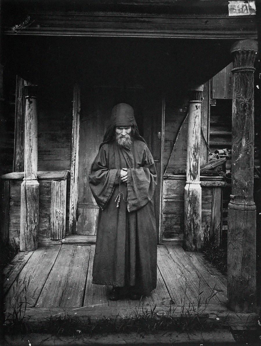 村の自宅前に立つ司祭