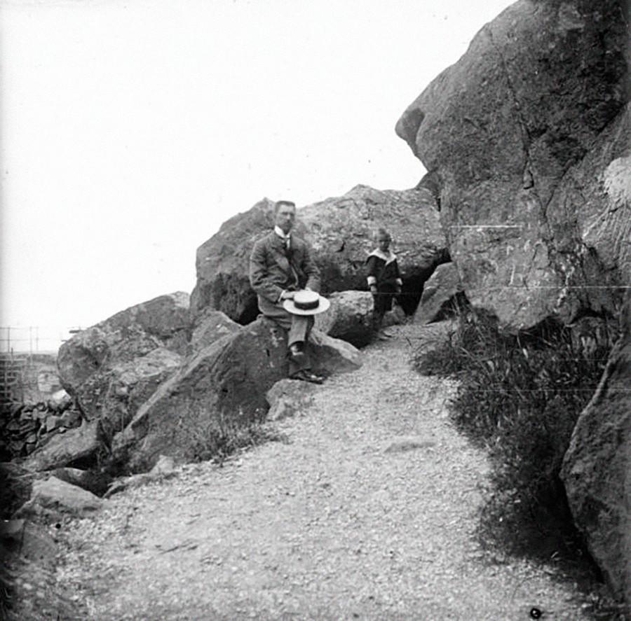 Un père et son fils grimpant sur les rochers à Aloupka, années 1890
