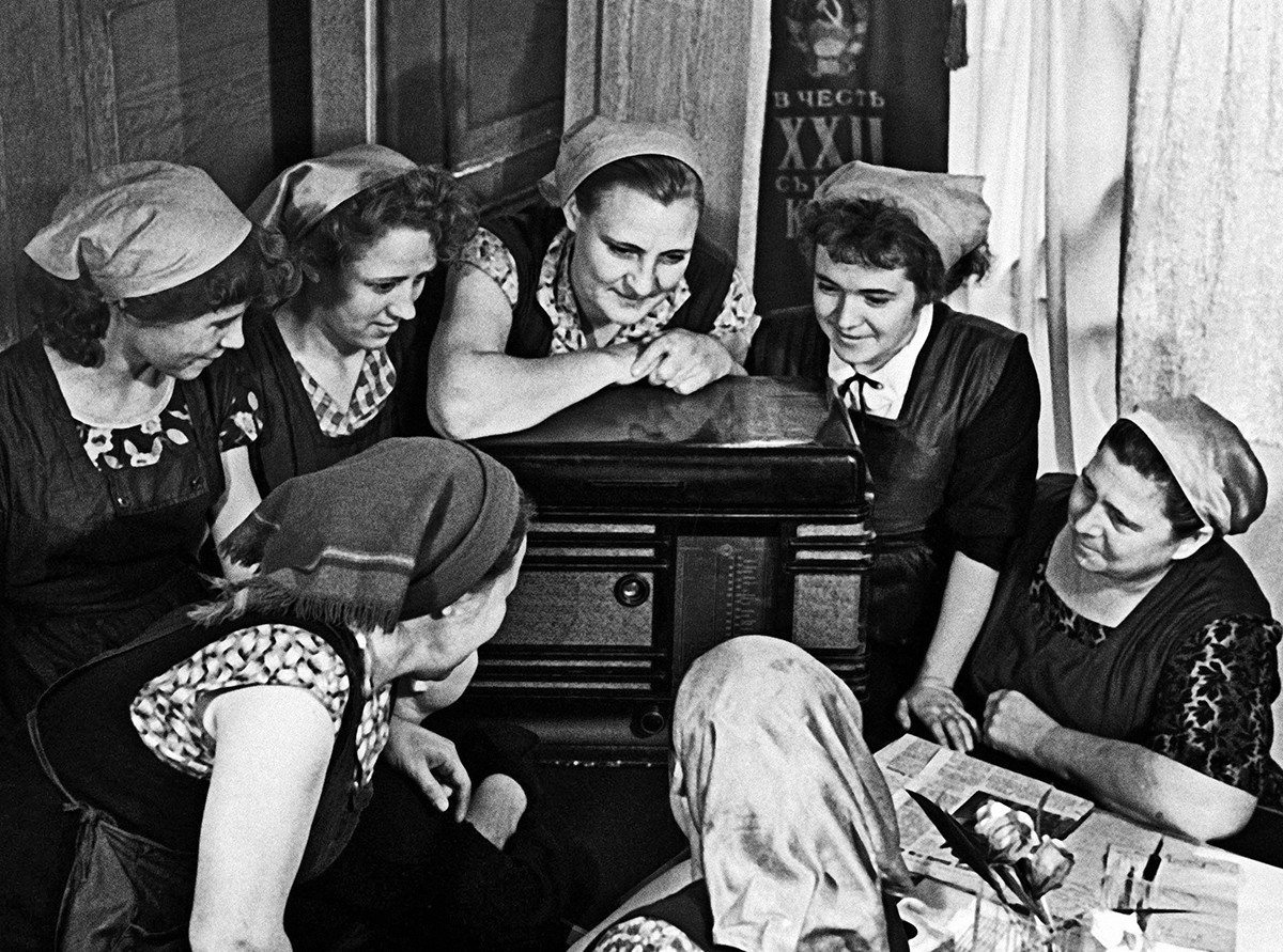 Lavoratori di una fabbrica di abbigliamento ascoltano un servizio radiofonico sul volo di Gagarin