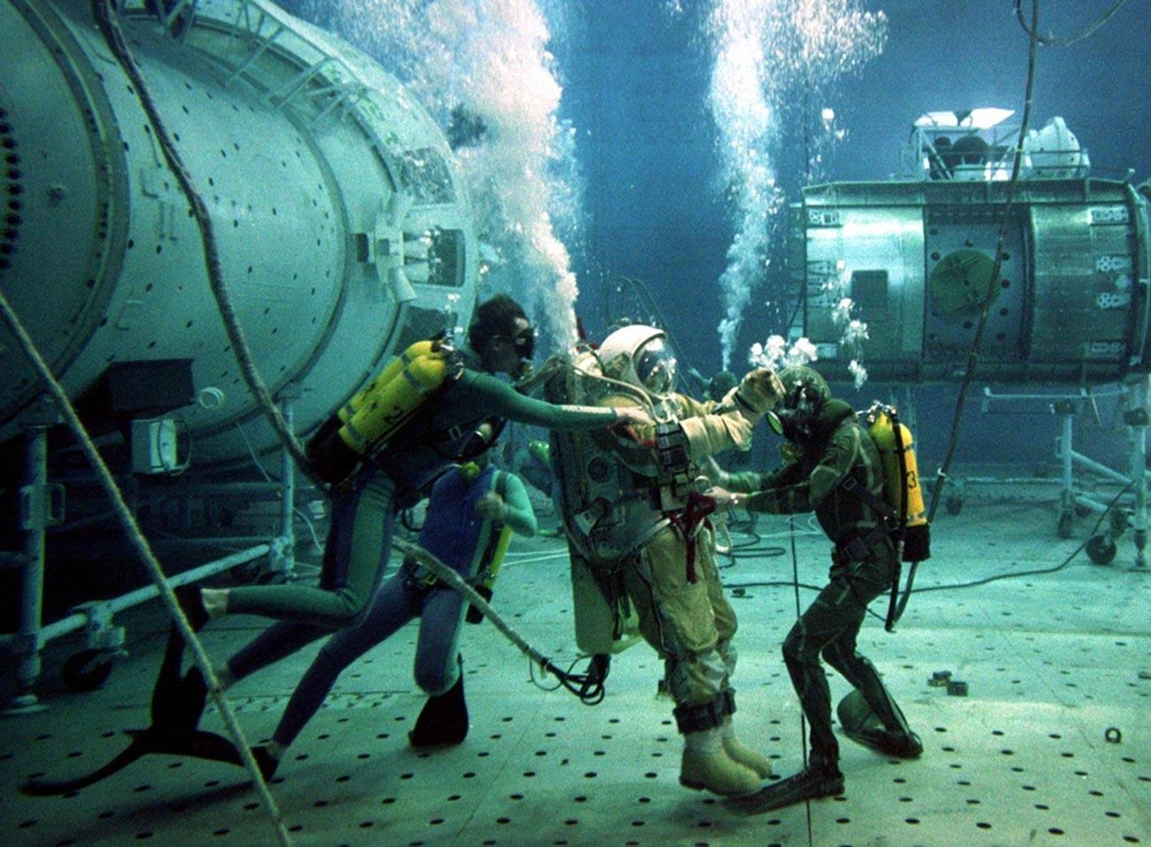 Instrutor de teste russo Oleg Puchkar é auxiliado por mergulhadores durante testes subaquáticos em uma réplica da estação espacial Mir danificada, em 4 de julho de 1997