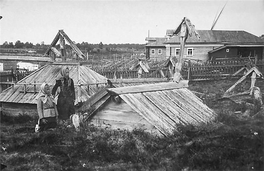 Groblje starovjeraca s križevima i malim kosim građevinama poput krovova na grobovima na obali Bijelog mora. Fotografija prije 1917.