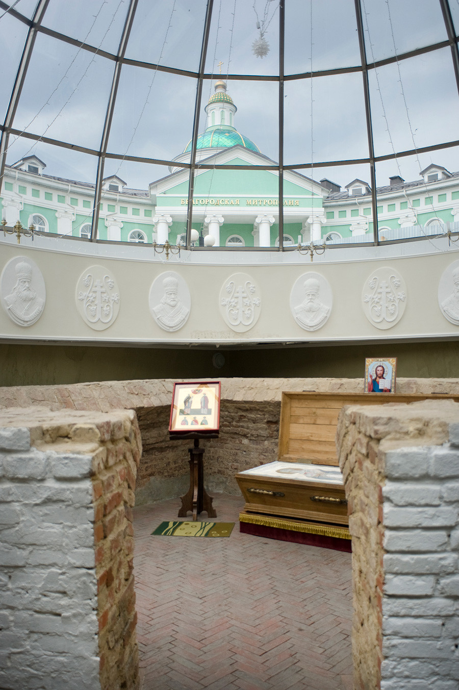 Burial crypt of Ioasaph, adjacent to the Chapel of St. Ioasaph. Located at the southwest part of the demolished Trinity Cathedral. Discovered by archeologists in 1911. Upper background: Belgorod Metropolitanate headquarters. June 24, 2015