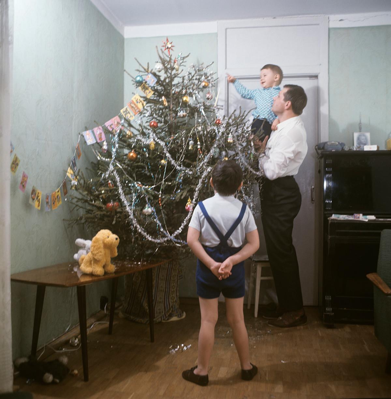 Un père et ses fils décorent un sapin du Nouvel An.