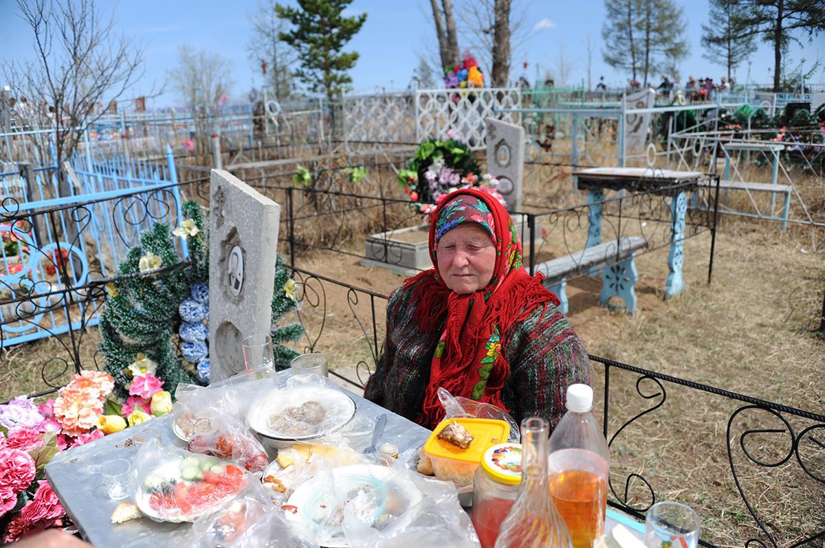 Seorang wanita tengah berziarah di pemakaman Desa Novotroitsk, Zabaykalsky Krai, pada Hari Peringatan (Radonitsa).