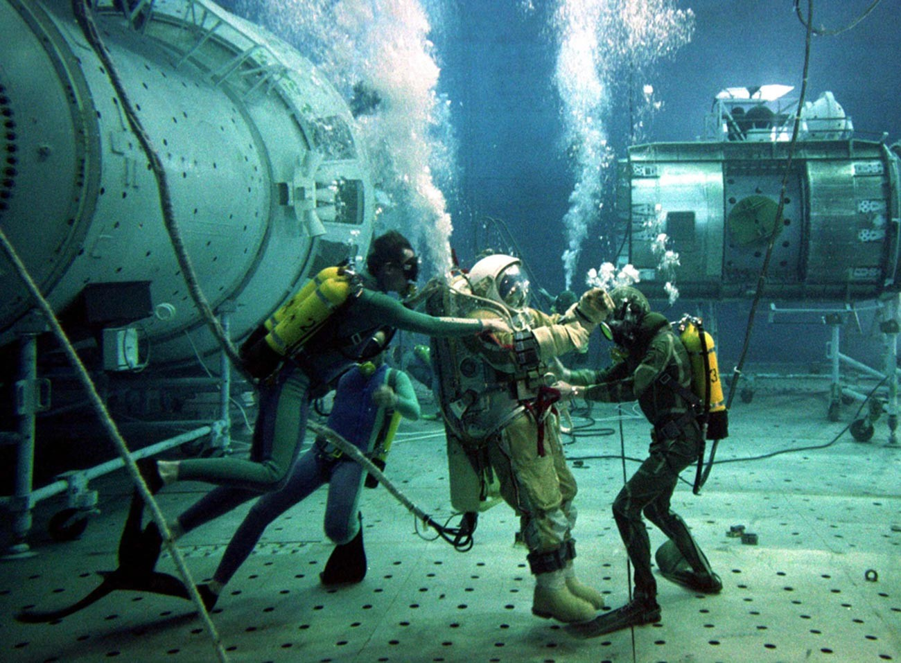 El instructor de pruebas ruso Oleg Pushkar es asistido por buzos durante las pruebas subacuáticas en una réplica de la estación espacial Mir dañada el 4 de julio de 1997.