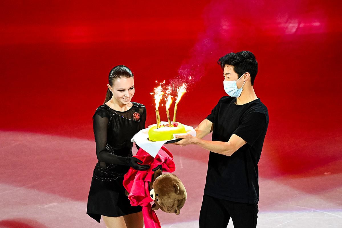 Nathan Chen (direita), dos EUA, dá um bolo de aniversário para Anna Scherbakova pelo seu 17º aniversário durante o Mundial em Estocolmo, em março de 2021