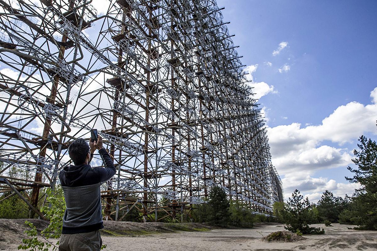 """Чернобил, Украина, 27 април 2016 година; Посетител го фотографира радарскиот систем """"Дуга"""" што СССР го користеше во Чернобил. Чернобилската катастрофа се случи на 26 април 1986 година во Чернобилската нуклеарна електрана."""