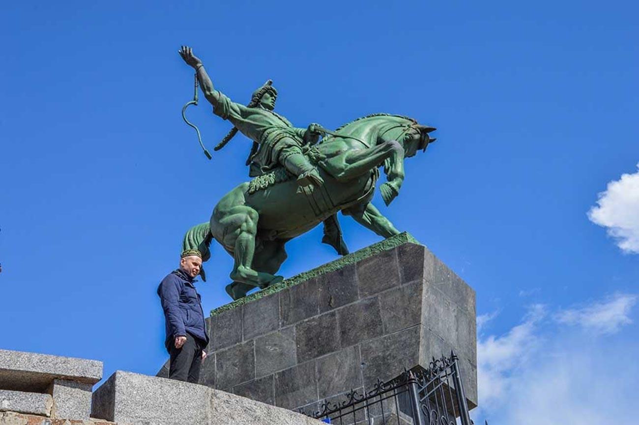 Seorang pria dengan topi khas Bashkir berfoto di dekat monumen Salavat Yulayev.
