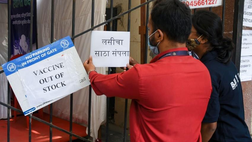 """Profissional de saúde coloca cartaz, no qual lê-se """"vacina fora de estoque"""", em um centro de vacinação em Mumbai"""