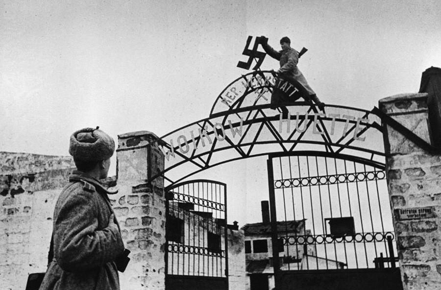 Des soldats soviétiques arrachent la croix gammée des portes de l'usine Voïkov à Kertch, en Crimée, 1944