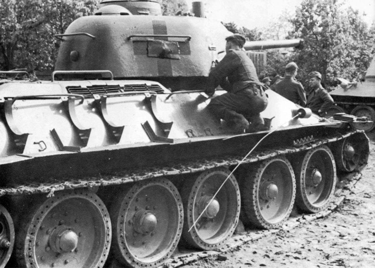 Немачки тенкиста уцртава немачке знаке распознавања на куполу заплењеног совјетског тенка Т-34-76.