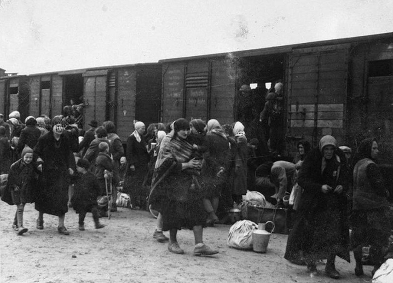 Orang-orang menaiki kereta ke tempat relokasi.