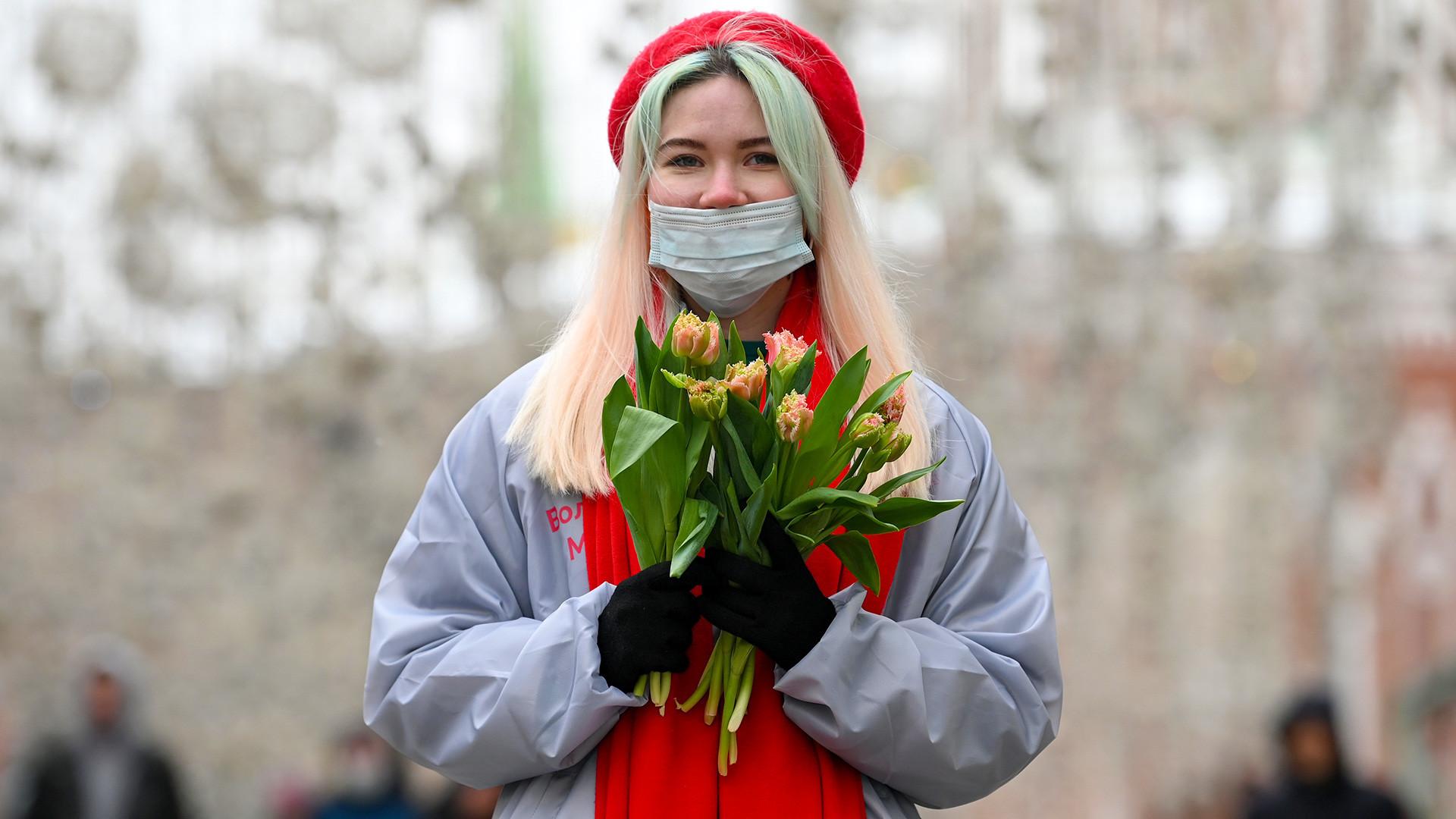 """Волонтерка на Никољската улица им дели лалиња на жените. Акцијата """"Вам сакани"""" по повод 8 март се одржува на железничките и на метро станиците, на булеварите, на плоштадите и во парковите на Москва. 500 волонтери за време на оваа акција делат над 300.000 лалиња."""