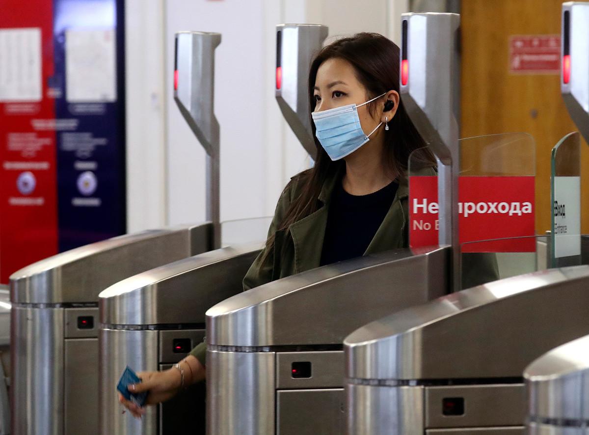 """Жена минува покрај турникет на станицата """"Молодјожнаја"""" на московското метро, 3 октомври 2020 година."""