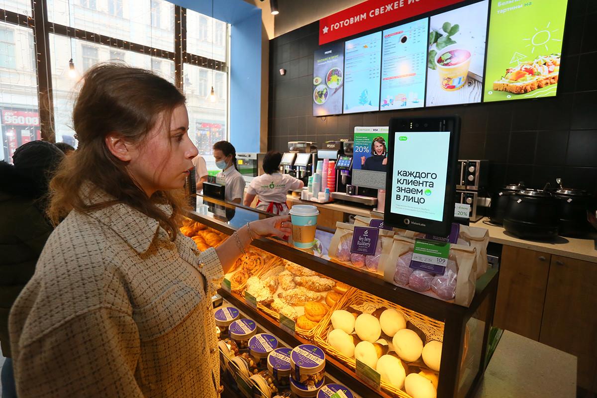 Cliente d'un café de la chaîne PRIME, à Moscou, à côté de la caisse où est installé un dispositif de paiement biométrique