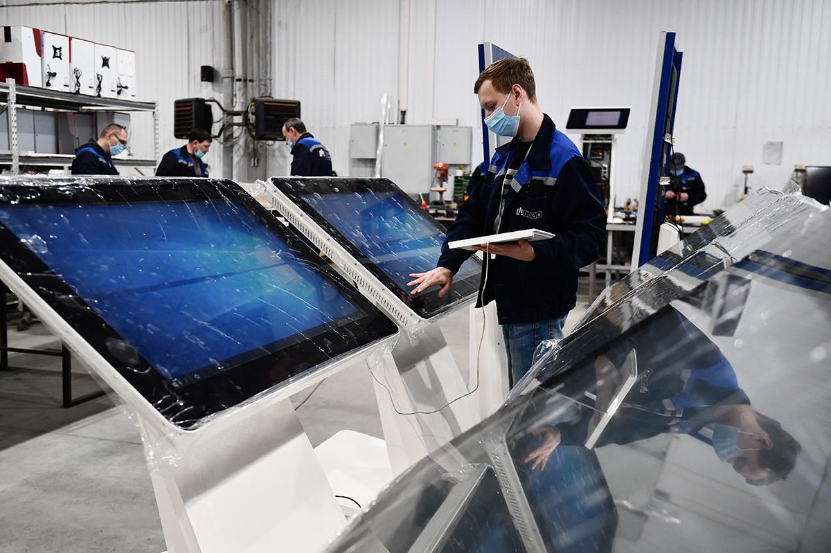 Работник на обект за производство на безконтактни дезинфектанти и мултимедийно оборудване за завода на LIGA в Екатеринбург
