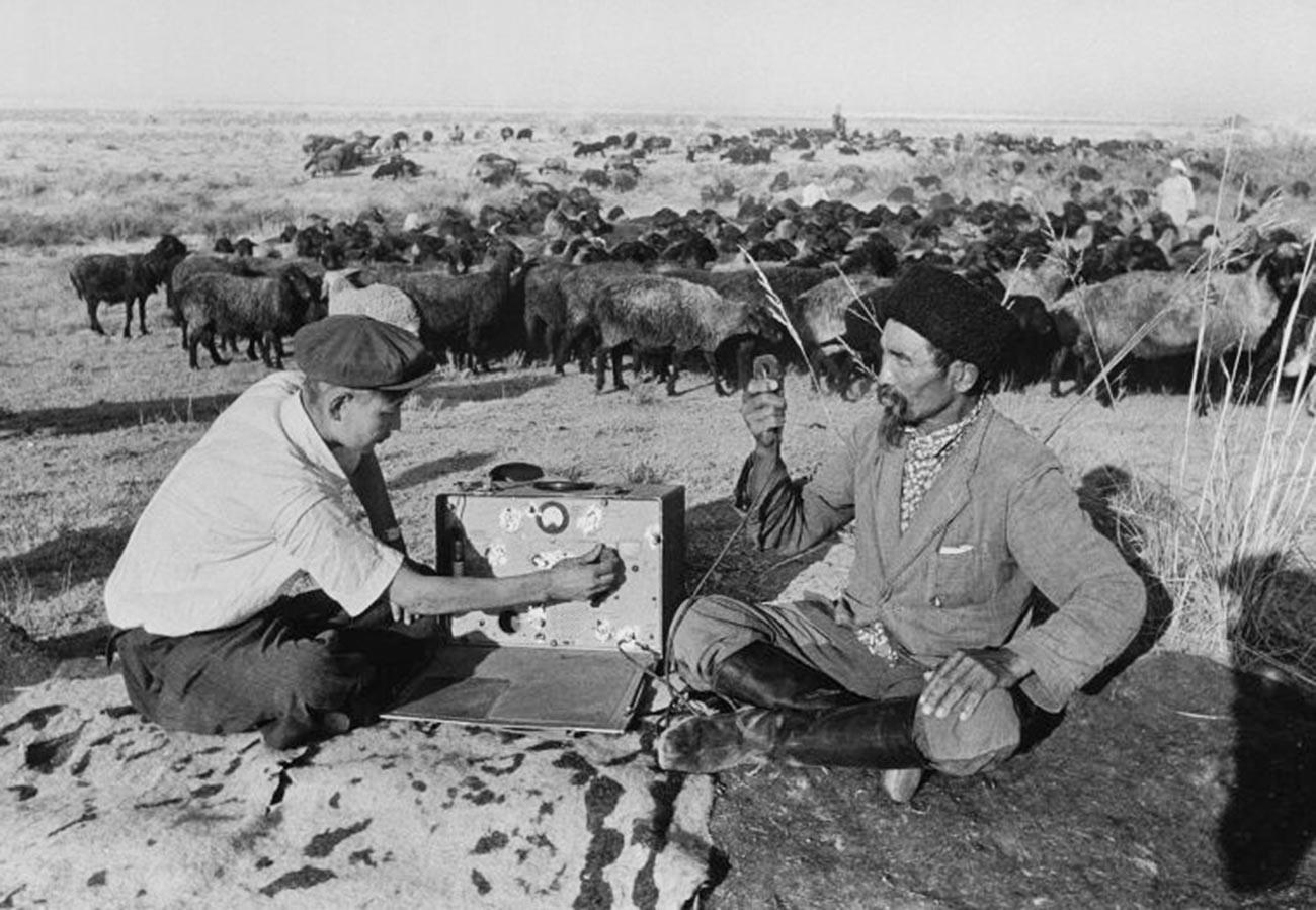 Penggembala ternak tengah mendengarkan radio disela menggembala di lahan yang baru dibuka di Kazakhstan, 1952.