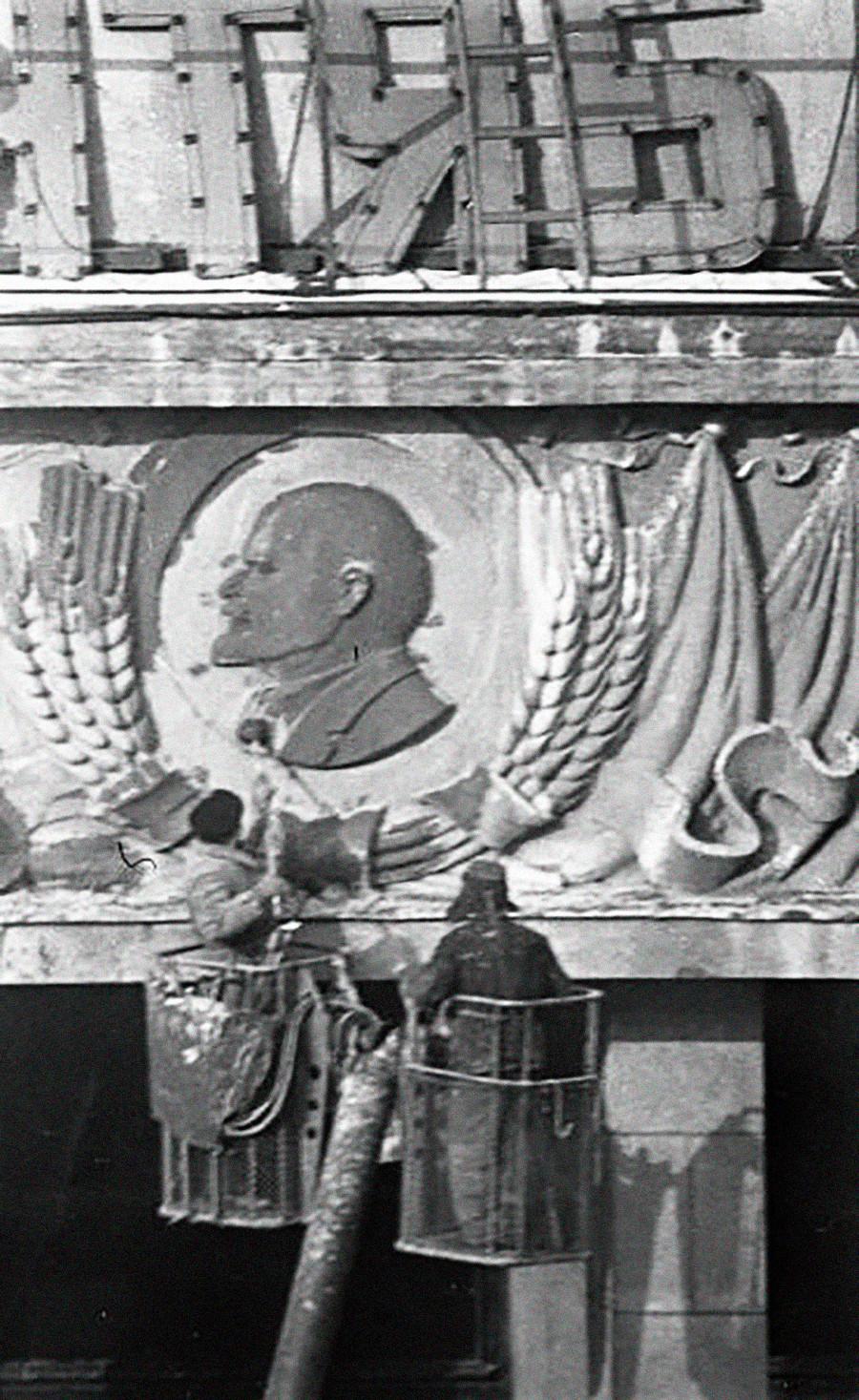 Zwei Arbeiter reinigen das Lenin-Porträt in einem Kolchos.