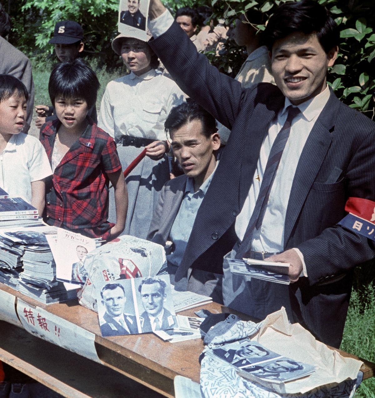 ガガーリンを歓迎する東京の人々。集まった人々にソ連初の宇宙飛行士であるユーリー・ガガーリンとゲルマン・チトフの写真を配るボランティアスタッフ