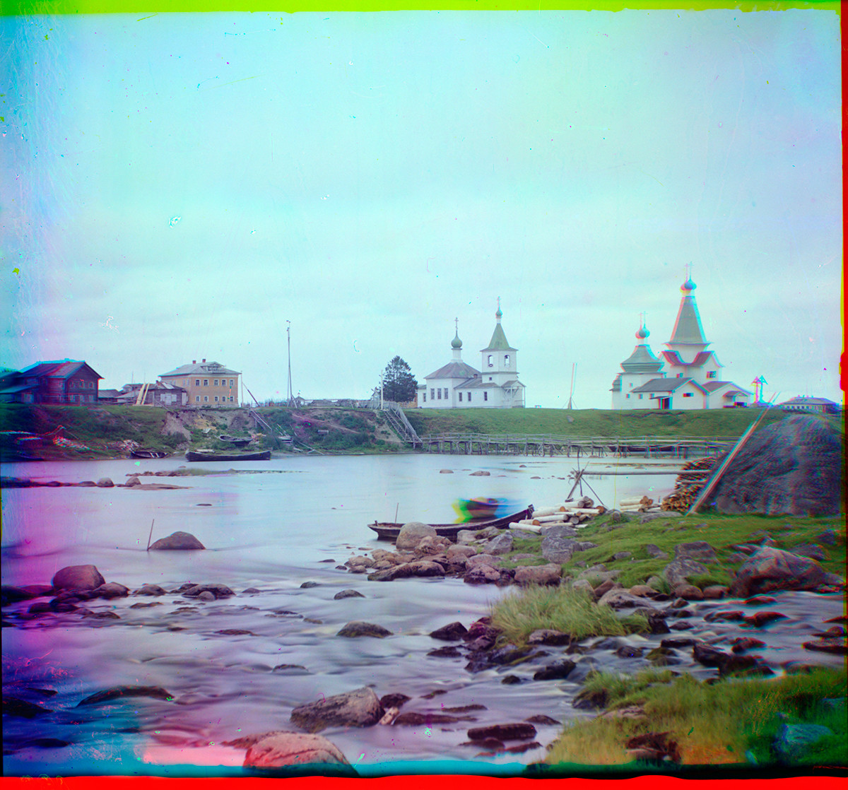 Shuyeretskoye. View across Shuya River with wooden Church of St. Clement (center), Church of St. Paraskeva & St. Nicholas Church. Smudge in the skiff is a person moving during the three exposures of the color process. Summer 1916