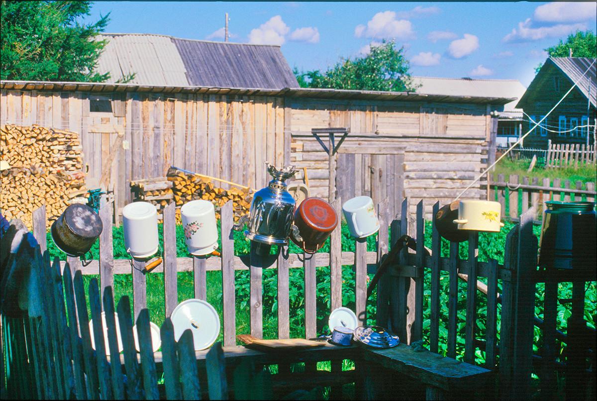 Varzouga. Cour latérale d'une maison sur la rive gauche.Des pots lavés et un samovar sèchent sur la clôture