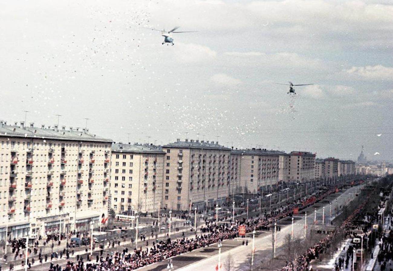 Des hélicoptères larguent des dépliants de bienvenue à l'intention du héros cosmonaute au-dessus de la ville