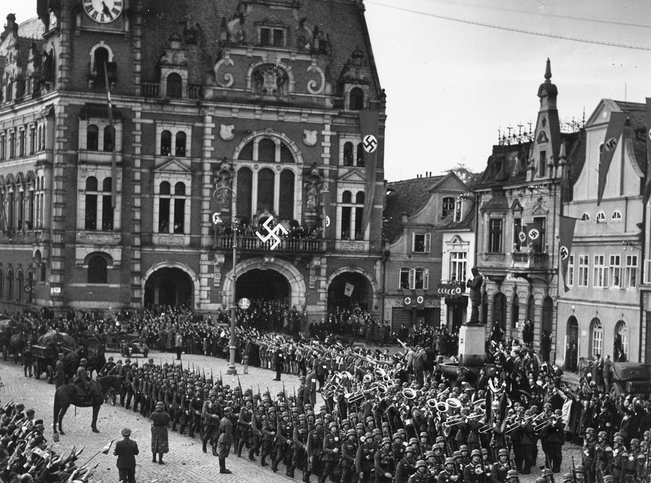 Truppen der deutschen Armee marschieren in das tschechoslowakische Gebiet ein und stellen sich auf dem mit Hakenkreuzbannern geschmückten Stadtplatz in Rumburk zum Appell auf.