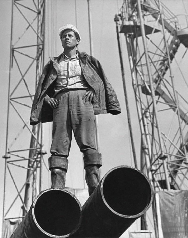 Un operaio petrolifero posa dei tubi in Siberia