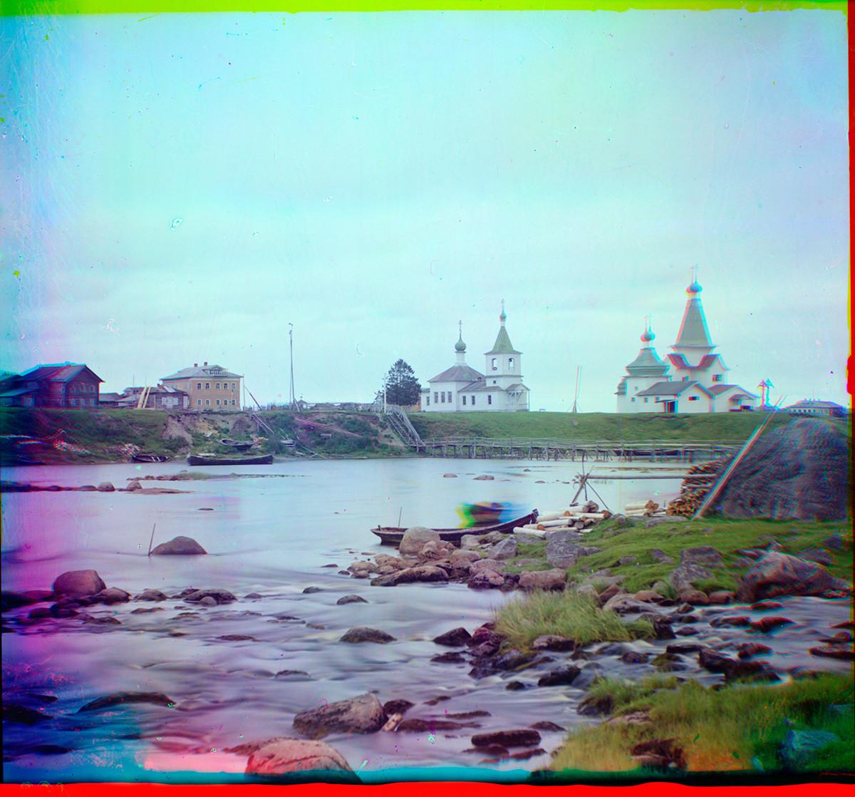 Šujereckoje. Pogled na reko Šuja z leseno cerkvijo sv. Klementa (v sredini), cerkvijo sv. Paraskeve in cerkvijo sv. Nikolaja. Madež na čolnu je oseba, ki se premika med tremi ekspozicijami barvnega postopka. Poletje 1916