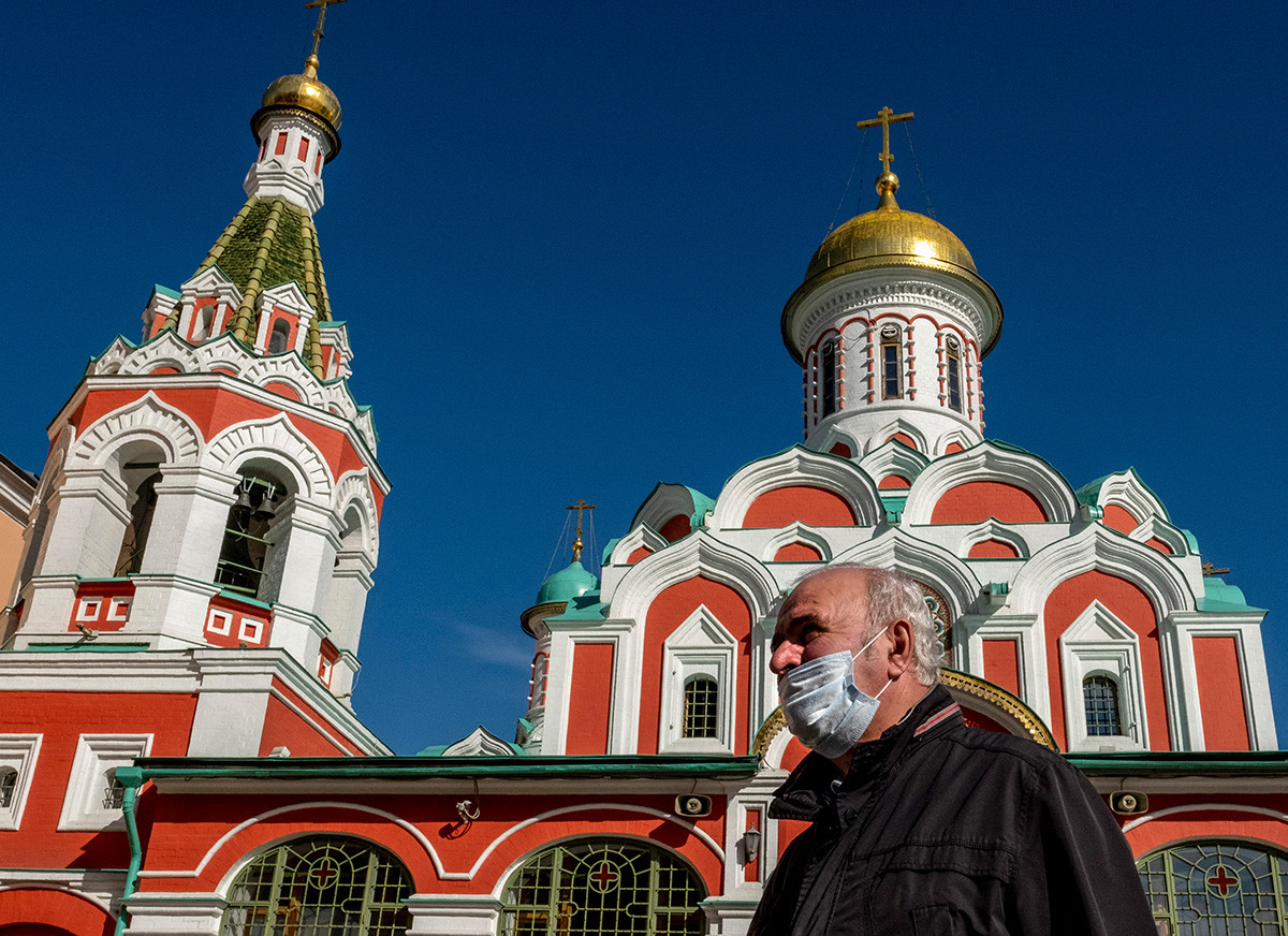 Пролазник са заштитном маском на лицу испред руског православног храма на Црвеном тргу у центру Москве, 2. октобар 2020.