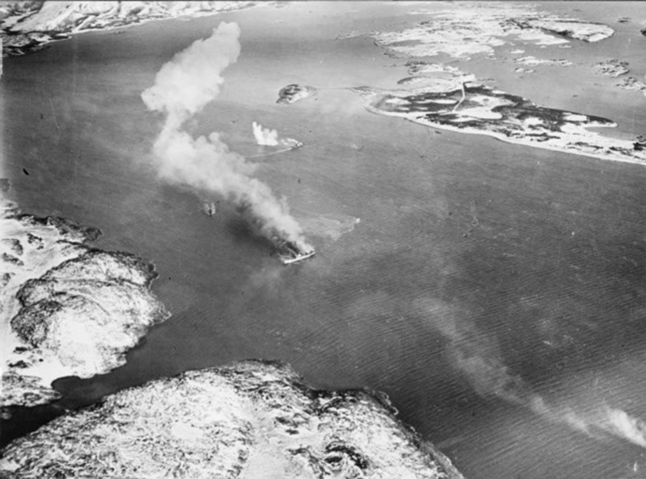"""Теретни брод """"Ригел"""" који је био у служби немачке армије и патролни чамци из његове пратње у пламену после бомбардовања."""