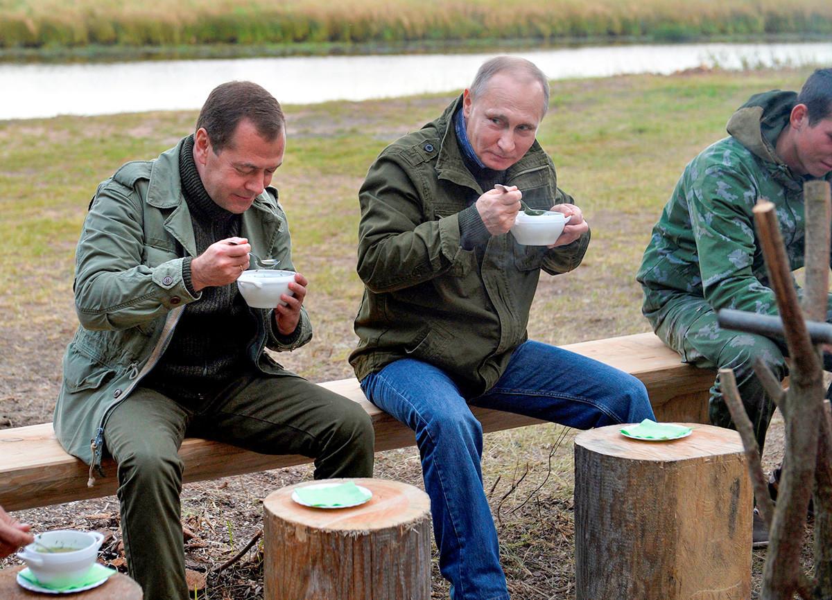 Presiden Rusia Vladimir Putin (tengah) dan Perdana Menteri Dmitry Medvedev (kiri) menyantap makanan setelah berkeliling Danau Ilmen di Novgorod, Rusia, 10 September 2016.