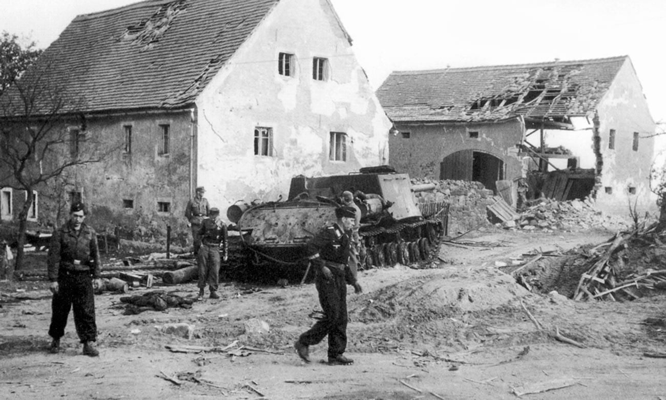 Немачки тенкисти разгледају уништен пољски самоходни тенк ИСУ-122 у насељу близу Бауцена.