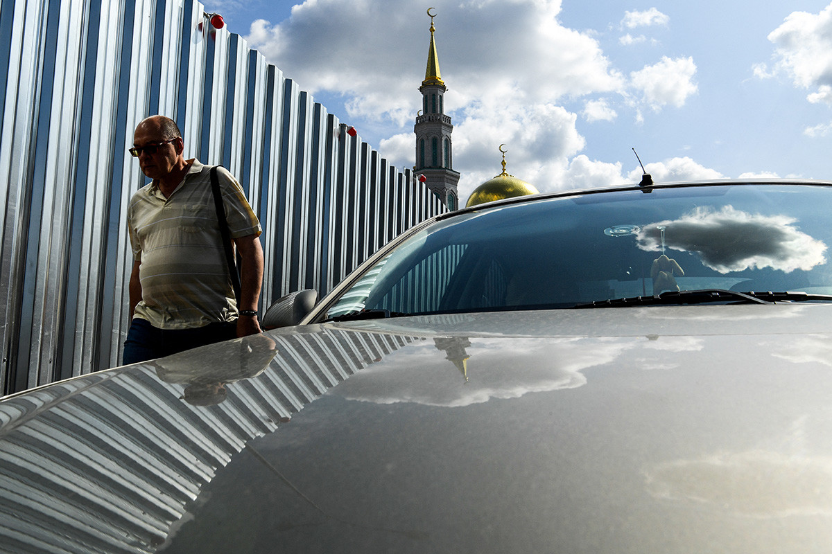 A man walks past a metal fence surrounding a construction site near Moscow's Sobornaya mosque on August 7, 2019