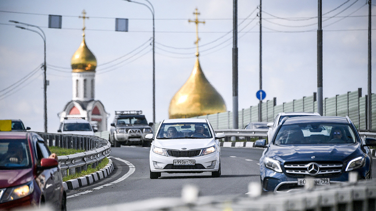 Cars move along a motorway in the Moscow satellite town of Odintsovo on June 17, 2019, as the Cathedral of Saint George the Victorious is seen in the background